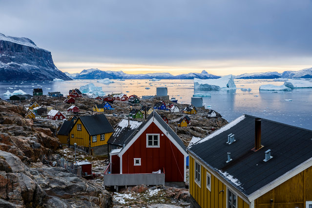 """Uummannaq. """"This is a small island in Greenland, home to about 1,200 people. It was really a treat waking up with such views of the colourful houses, with the icebergs in the fjord as a backdrop. They say you leave a piece of your heart behind when you leave Uummannaq ... it is true"""". (Photo by Rayann Elzein/NatGeo Cities Travel Photographer of the Year 2017)"""