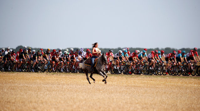 A woman rides a horse along the pack of riders passing through during the 216-kilometer Stage 6 Tour de France cycling race from Vesoul to Troyes, France on July 6, 2017. (Photo by Christian Hartmann/Reuters)