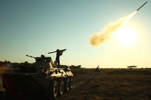 "A soldier fires a portable air defense rocket during the International military games ""Masters of Antiaircraft Battle – 2015"" outside the Russian southern town of Yeisk on August 6, 2015. Teams of the Armed Forces of the People's Republic of China, the Islamic Republic of Pakistan, the Bolivarian Republic of Venezuela, the Republic of Belarus and the Russian Federation take part in the military competition. (Photo by Sergei Venyavsky/AFP Photo)"