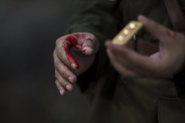 """An actor with fake blood on his hands holds a military epaulette as he prepares for a scene during filming of """"The Last Prince"""" television series at Hengdian World Studios near Hengdian July 23, 2015. (Photo by Damir Sagolj/Reuters)"""