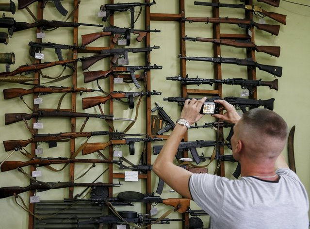 A visitor takes picture of weapons at an exhibition at Phaeton museum in Zaporizhia, Ukraine, August 11, 2015. (Photo by Gleb Garanich/Reuters)