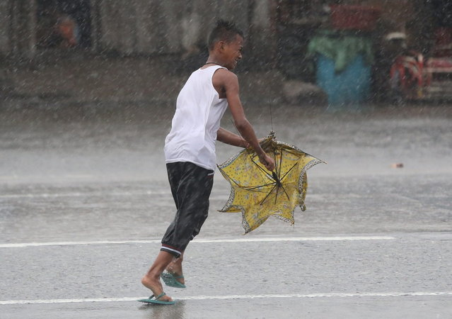 The umbrella of a Filipino boy is broken by strong winds as he crosses a street while Typhoon Rammasun batters suburban Navotas, north of Manila, Philippines on Wednesday, July 16, 2014. Typhoon Rammasun knocked out power in many areas but it spared the Philippine capital, Manila, and densely-populated northern provinces from being directly battered Wednesday when its fierce wind shifted slightly away, officials said. (Photo by Aaron Favila/AP Photo)