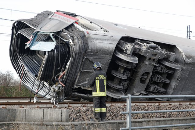 A firefighter inspects a derailed train carriage, near Lodi, northern Italy, Thursday, February 6, 2020. Italian authorities say a high-speed passenger train has derailed in northern Italy, killing two railway workers and injuring 27 people. (Photo by Antonio Calanni/AP Photo)
