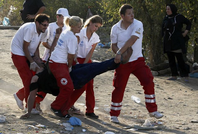 A Syrian refugee is carried by medics after collapsing at the Greek-Macedonian border, near the village of Idomeni, August 21, 2015. (Photo by Yannis Behrakis/Reuters)