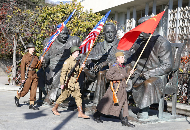 """Participants dressed as WWII soldiers with the flags of the United Kingdom, the United States and the Soviet Union walk past a monument to the """"Big Three"""" – UK Prime Minister Winston Churchill, US President Franklin Roosevelt, and Soviet leader Joseph Stalin – at Livadia Palace in Yalta, Russia on February 4, 2020. Russia is celebrating the 75th anniversary of the Yalta Conference (also known as the Crimean Conference), which was attended by the three leaders of the Allied nations in 4-11 February 1945, before the end of WWII. (Photo by Sergei Malgavko/TASS)"""