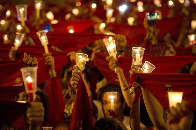 "People holding candle lights sing the traditional ""Poor of me"" (Pobre de mi) during the closing ceremony of the Festival of San Fermin at the Castle Square in Pamplona, northern Spain, 14 July 2016. The festival, locally known as Sanfermines, is held annually from 06 to 14 July in commemoration of the city's patron saint. (Photo by Villar Lopez/EPA)"