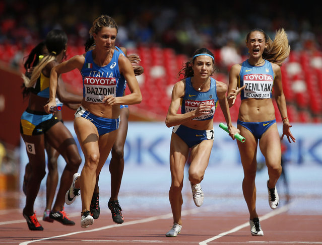 Chiara Bazzoni of Italy (L) and Olha Lyakhova of Ukraine (2nd R) receive the baton during the final handover of their women's 4 x 400 metres relay heat at the 15th IAAF Championships at the National Stadium in Beijing, China August 29, 2015. (Photo by Lucy Nicholson/Reuters)