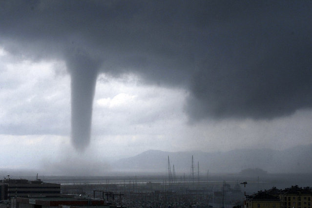 A tornado is seen approaching the costal city of Genoa, in Northern Italy, Tuesday, August 19, 2014. At right, in background, the profile of the Costa Concordia cruise liner wreck which was towed to Genoa for scrapping. Tornadoes and thunderstorms hit Genoa and the Liguria region coast Tuesday, causing damages to seaside cabins and floods but no victims. (Photo by Tano Pecoraro/AP Photo)