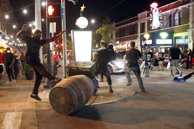Protesters overturn trash cans as police try to clear a violent crowd Saturday, September 16, 2017, in University City, Mo. Earlier, protesters marched peacefully in response to a not guilty verdict in the trial of former St. Louis police officer Jason Stockley. (Photo by Jeff Roberson/AP Photo)