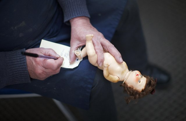 "Geoff Chapman, ""Head Surgeon"" and third-generation owner of Sydney's Doll Hospital, holds a small doll on one hand as he writes details onto its repair card attached to its foot, at his workshop June 28, 2014. (Photo by Jason Reed/Reuters)"
