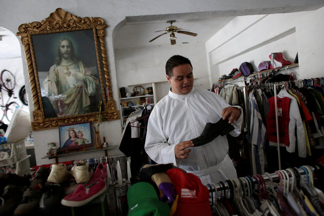 An aspiring Catholic priest Jose Luis Guerra, a member of Raza Nueva in Christ, a project of the archdiocese of Monterrey, checks shoes at a second hand shop, in Monterrey, Mexico, July 13, 2016. (Photo by Daniel Becerril/Reuters)