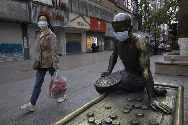 In this April 13, 2020, photo, a resident walks through a partially closed retail street with a bronze statue covered with a face mask in Wuhan in central China's Hubei province. Chinese leaders have reopened factories and shops in an effort to revive the economy, but the consumers whose spending propels most of China's growth have been slow to return to shopping malls and auto dealerships. (Photo by Ng Han Guan/AP Photo)