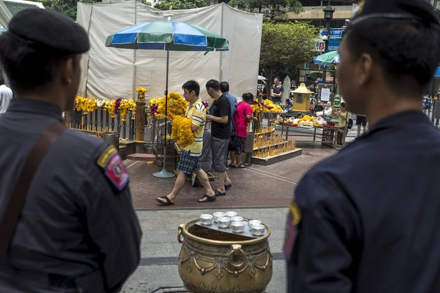 Police officers stand guard as people pray at the Erawan shrine, the site of recent deadly blast, in central Bangkok, Thailand, September 3, 2015. (Photo by Athit Perawongmetha/Reuters)