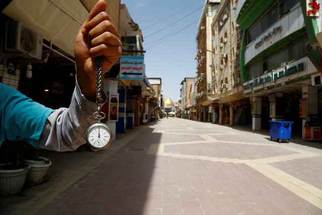 A man holds a pocket watch at noon, as he shows the time while posing for photo at an almost empty market near the Imam Ali shrine, during the coronavirus disease (COVID-19) outbreak, in Najaf, Iraq, March 31, 2020. (Photo by Alaa al-Marjani/Reuters)