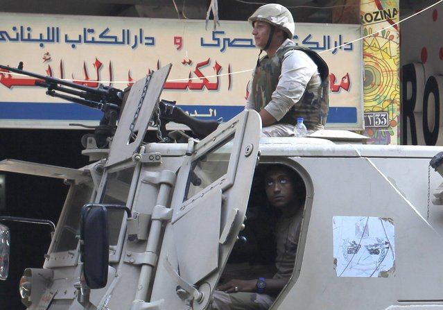 Army soldiers stand guard in their military vehicle in central Cairo ahead of expected protests,  August 30, 2014. (Photo by Asmaa Waguih/Reuters)