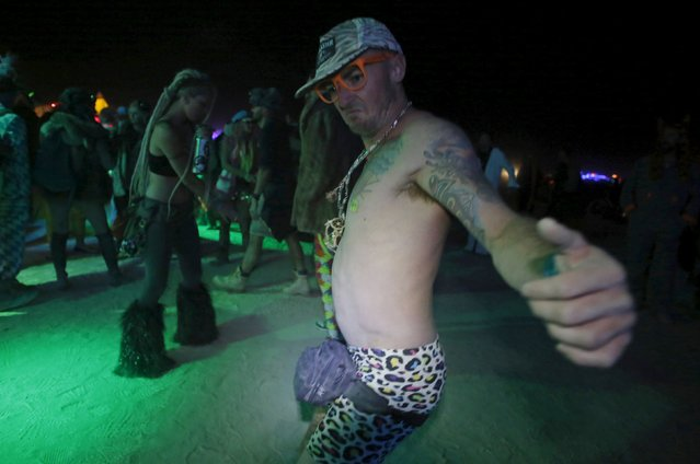 """A participant dances on the Playa during the Burning Man 2015 """"Carnival of Mirrors"""" arts and music festival in the Black Rock Desert of Nevada September 5, 2015. (Photo by Jim Urquhart/Reuters)"""