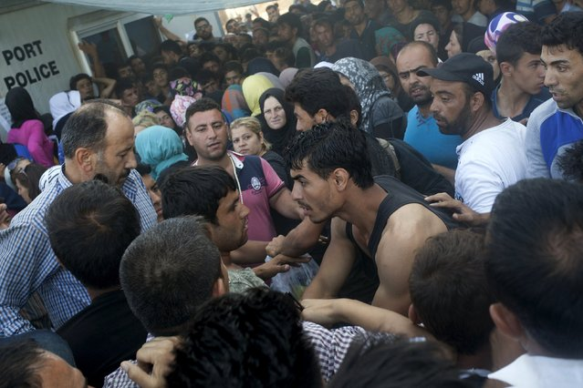 Afghan and Syrian refugees scuffle over priority for a registration procedure at the port of Mytilene on the Greek island of Lesbos, September 6, 2015. (Photo by Dimitris Michalakis/Reuters)