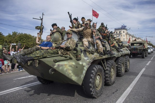 Pro-Russian rebels ride on an armored personnel carrier (APC) during a parade in Luhanks, eastern Ukraine, September 14, 2014. (Photo by Marko Djurica/Reuters)