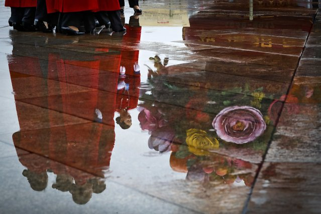 "Hospitality staff are reflected in a puddle of water as they prepare to pose for photograph in front of a giant basket decorated with replicas of flowers and fruits on display on Tiananmen Square during the opening ceremony of the 19th Party Congress in Beijing, Wednesday, October 18, 2017. Chinese President Xi Jinping on Wednesday urged a reinvigorated Communist Party to take on a more forceful role in society and economic development to better address ""grim"" challenges facing the country as he opened a twice-a-decade national congress. (Photo by Andy Wong/AP Photo)"