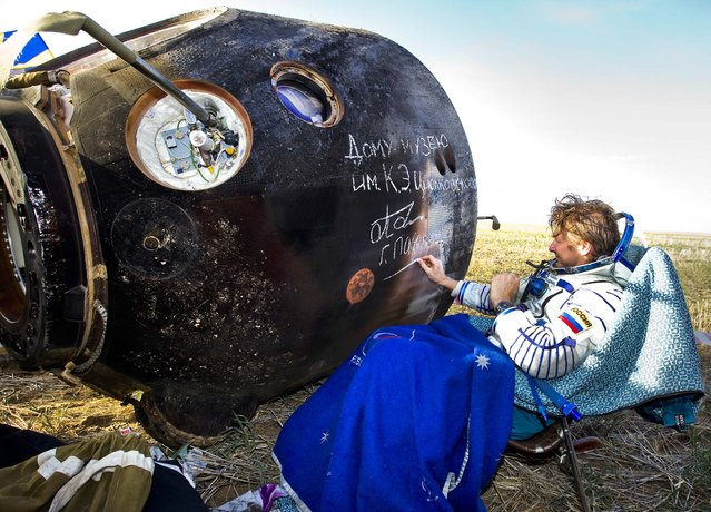 Russian cosmonaut Gennady Padalka signs an autograph on the Soyuz capsule after landing near the town of Arkalyk in northern Kazakhstan, on September 17, 2012. The capsule returned a trio of astronauts from a four-month stint on the International Space Station. (Photo by Shamil Zhumatov/Pool)