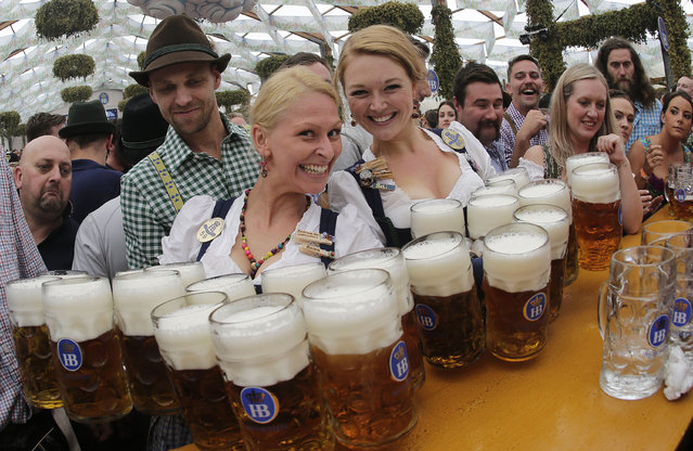 Waitresses Beli, right, and Anika pose with beer mugs during the opening of the 181th Oktoberfest beer festival in Munich, southern Germany, Saturday, September 20, 2014. (Photo by Matthias Schrader/AP Photo)