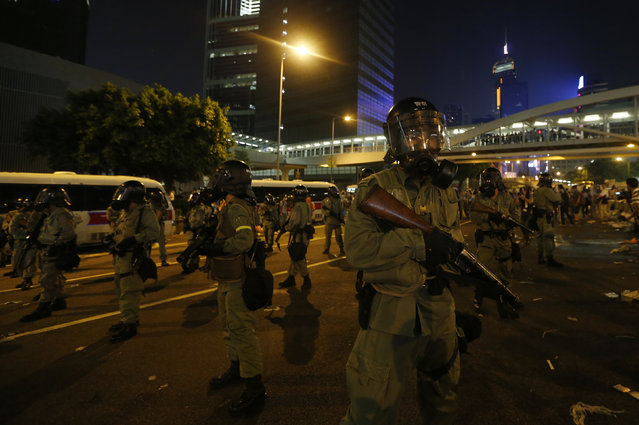 Riot policemen with tear gas launchers stand guard as protesters block the main street to the financial Central district outside the government headquarters in Hong Kong, September 28, 2014. (Photo by Tyrone Siu/Reuters)