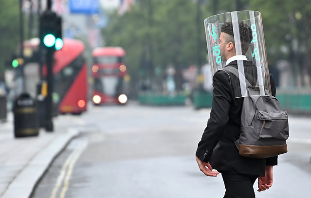 A pedestrian wearing a form of PPE (personal protective equipment) of a perspex full-face covering, as a precautionary measure against COVID-19, walks across Oxford Street in central London on June 11, 2020, as non-essential shops prepare to re-open on June 15. Britain's current guidelines on social distancing remain at two metres (2M), but business leaders and some politicians are on Thursday calling for it to be reduced to one (1M), or one-and-a-half (1.5M) metres. (Photo by Justin Tallis/AFP Photo)