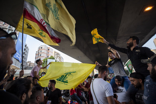 Hezbollah and Amal supporters wave Hezbollah and Iranian flags as they shout slogans against Israel and U.S. during a protest in the southern suburb of Beirut, Lebanon, Sunday, June 28, 2020. The protest came hours after Lebanon's foreign minister summoned the U.S. ambassador to Beirut over comments, she made recently in which she criticized Hezbollah. The meeting between Foreign Minister Nassif Hitti and Ambassador Dorothy Shea is scheduled for Monday afternoon. (Photo by Hassan Ammar/AP Photo)