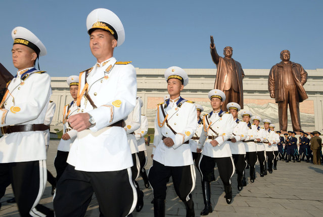 North Korean military personnel march as they visit the statues of late leaders, Kim Il Sung, left, and Kim Jong Il on Mansudae to mark the 69th anniversary of the founding of the ruling Workers' Party of Korea, in Pyongyang, North Korea Friday, October 10, 2014. (Photo by AP Photo/Kyodo News)