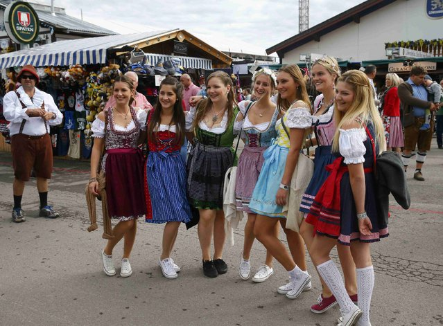Girls in traditional Bavarian outfits pose for a picture on the grounds of the 182nd Oktoberfest in Munich, Germany, September 19, 2015. (Photo by Michael Dalder/Reuters)
