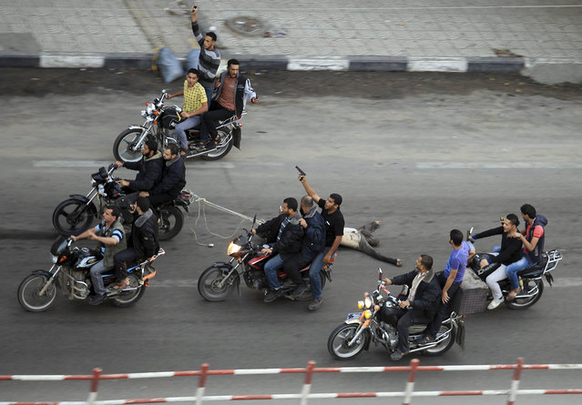 "Palestinian gunmen ride motorcycles as they drag the body of a man, who was suspected of working for Israel, in Gaza City November 20, 2012. Palestinian gunmen shot dead six alleged collaborators in the Gaza Strip who ""were caught red-handed"", according to a security source quoted by the Hamas Aqsa radio on Tuesday. (Photo by Suhaib Salem/Reuters)"