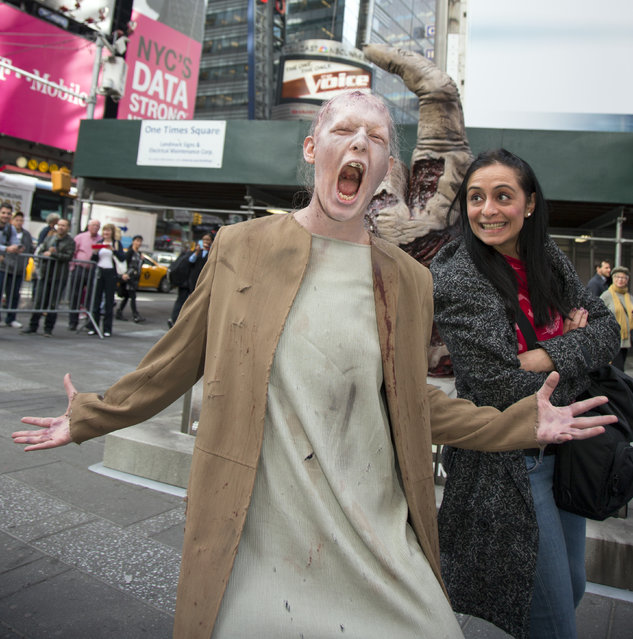 "Actors dressed up as zombies walk around while posing for photos with  passers-by in New York's Times Square on Friday, October 10, 2014 as a promotion for the season premiere of AMC's ""The Walking Dead"" this Sunday, October 12, 2014. (Photo by Gordon Donovan)"