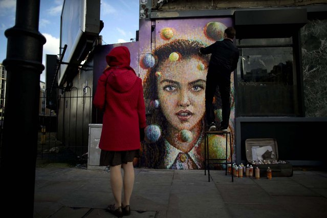 "A passerby watches Australian artist James Cochran, also known as Jimmy C, put finishing touches to his spray painted 3D piece ""Girl with Spheres in 3D"" on the outside wall of a cafe in east London, November 22, 2012. The effects of the 3D painting can only be seen when the viewer looks through a pair of 3D glasses, which the cafe will keep a stock of to lend to people. (Photo by Matt Dunham/Associated Press)"