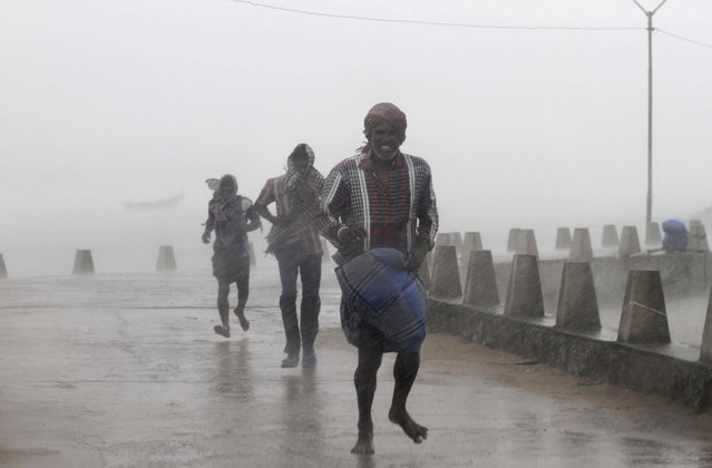 People run for shelter as heavy rain and wind gusts rip through the Bay of Bengal coast at Gopalpur, Orissa, about 285 kilometers (178 miles) north east of Visakhapatnam, India, Sunday, October 12, 2014. Trees were uprooted and power cables snapped as a powerful cyclone swept through the Bay of Bengal and slammed into the southern city of Visakhapatnam, one of two storms pounding Asia on Sunday. (Photo by Biswaranjan Rout/AP Photo)
