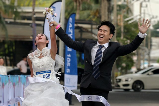 Naree Phavasanta, left, and Suparoek Charoenphol celebrate while crossing the finish line to win the Running of the Brides in Bangkok, Thailand, December 2, 2017. (Photo by Athit Perawongmetha/Reuters)