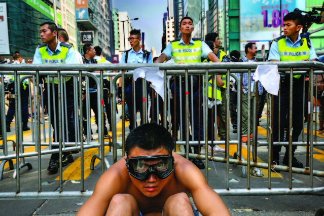 A protester sits front of barriers against police officers at a main street in Mong Kok district in Hong Kong Friday, October 17, 2014. Riot police cleared an offshoot Hong Kong pro-democracy protest zone in a dawn raid on Friday, taking down barricades, tents and canopies that have blocked key streets for more than two weeks, but leaving the city's main thoroughfare still in the hands of the activists. (Photo by Vincent Yu/AP Photo)