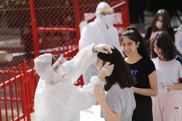 Health workers disinfect and hand masks to Turkish students of eighth grade before their High School Transition System (LGS) exams at the Fevzi Ozbey secondary school in Ankara, Turkey, 20 June 2020. (Photo by EPA/EFE/Stringer)