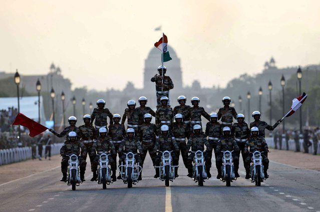 Indian army soldiers perform a daredevil motorcycle stunt during a parade to mark the 50th anniversary of the India-Pakistan war of 1965, in New Delhi, India, Sunday, September 20, 2015. (Photo by Tsering Topgyal/AP Photo)