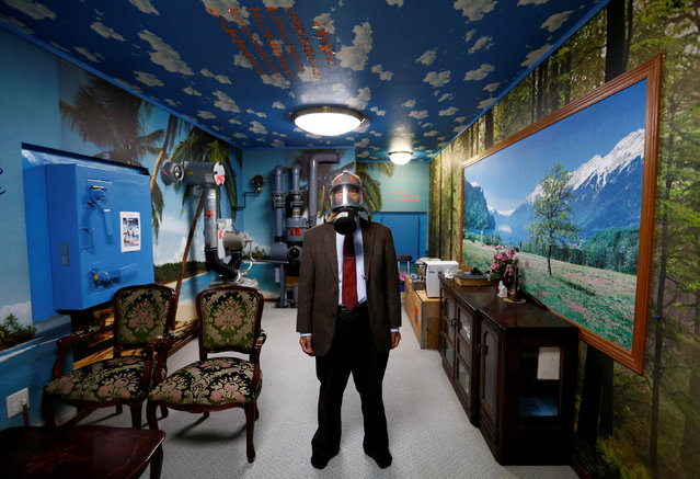 Seiichiro Nishimoto, CEO of Shelter Co., poses wearing a gas mask at a model room for the company's nuclear shelters in the basement of his house in Osaka, Japan on April 26, 2017. (Photo by Kim Kyung-Hoon/Reuters)