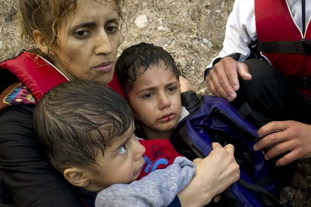 A Syrian refugee hugs her children following their arrival on an overcrowded dinghy in rough sea on the Greek island of Lesbos, after crossing a part of the Aegean Sea from the Turkish coast, October 2, 2015. (Photo by Dimitris Michalakis/Reuters)