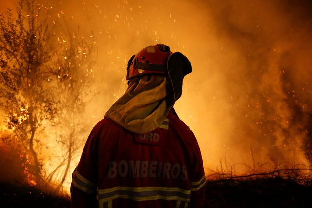 A firefighter is seen near flames from a forest fire in Cabanoes, near Lousa, Portugal, October 16, 2017. (Photo by Pedro Nunes/Reuters)