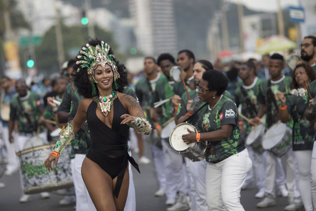 Members of a samba school warm up before parading along Copacabana Beach in Rio de Janeiro, Brazil, Saturday, January 6, 2018. (Photo by Leo Correa/AP Photo)