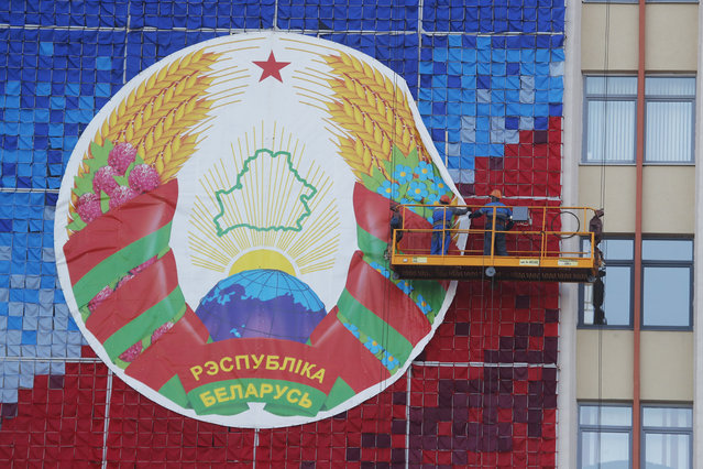 Municipal workers mount Belarusian national emblem on a building at Independent Square in Minsk, Belarus, Monday, August 24, 2020. (Photo by Dmitri Lovetsky/AP Photo)