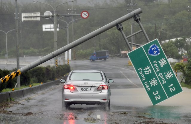 A car drives pass a collapsed traffic sign, toppled by strong winds of typhoon Meranti, as it slashes southern Taiwan on September 14, 2016. Parts of Taiwan were brought to a standstill on September 14, as the strongest typhoon of the year skirted past the island's southern tip, knocking out power for more than 180,000 households. (Photo by Sam Yeh/AFP Photo)
