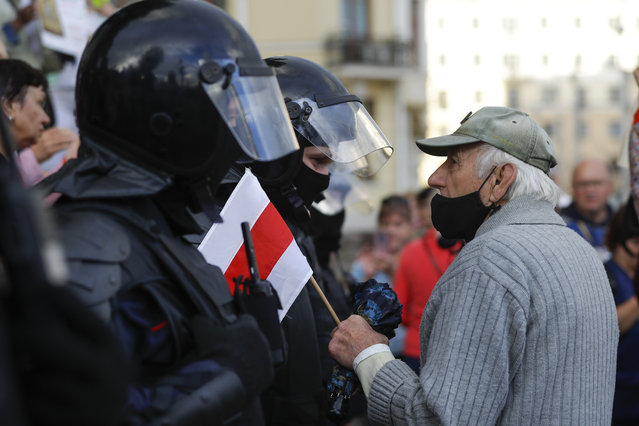 An elderly protester speaks to a policeman holding an old Belarusian national flag in front of riot police blocked Independence Square in Minsk, Belarus, Thursday, August 27, 2020. (Photo by Sergei Grits/AP Photo)