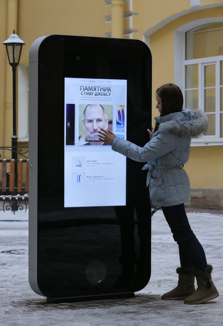In this file photo dated Thursday, January 10, 2013, a girl touches the screen showing a portrait of Steve Jobs on the recently erected memorial to late Apple Corp. co-founder in the courtyard of the Techno Park of the St. Petersburg National Research University of Information Technologies, Mechanics and Optics (ITMO University) in St. Petersburg, Russia. (Photo by Dmitry Lovetsky/AP Photo)