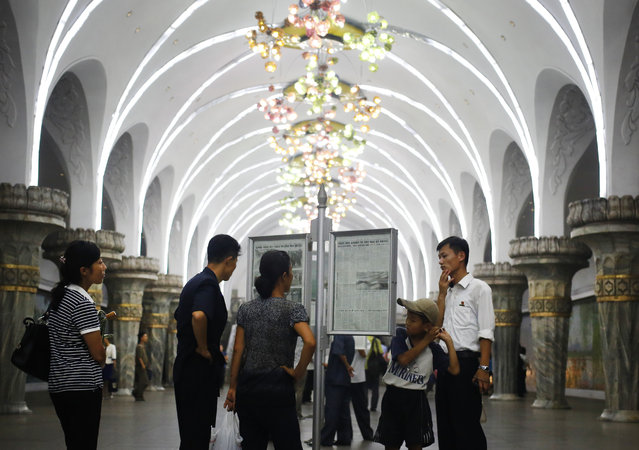 In this Sunday, August 23, 2015 photo, North Koreans read the public copy of a daily newspaper on the platform of a subway station in Pyongyang, North Kroea. (Photo by Dita Alangkara/AP Photo)