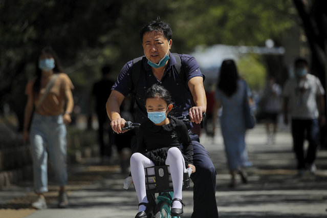 A man and a child wearing face masks to help curb the spread of the coronavirus ride a bicycle of bike-sharing companies in Beijing, Monday, August 24, 2020. China has gone eight days without reporting a new local case of COVID-19, with the Beijing International Film Festival among public events that are returning. (Photo by Andy Wong/AP Photo)