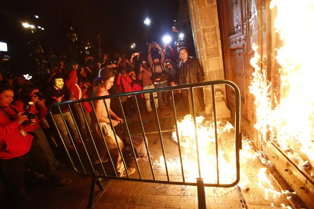 A group of protesters set fire to the wooden door of Mexican President Enrique Pena Nieto's ceremonial palace, during a protest denouncing the apparent massacre of 43 trainee teachers, in the historic center of Mexico City late November 8, 2014.(Photo by Edgard Garrido/Reuters)