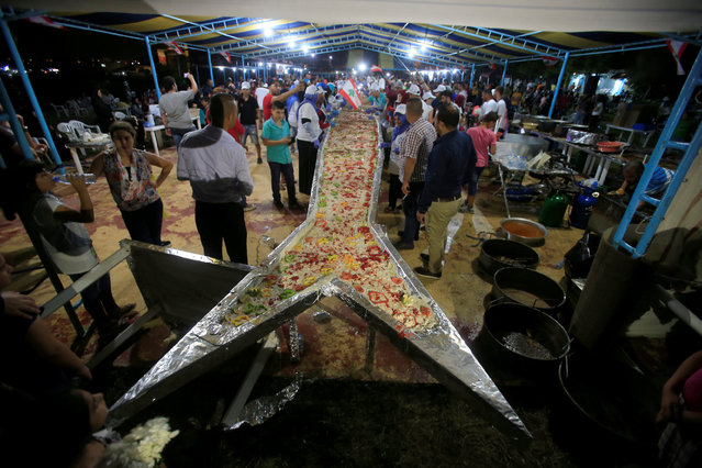 People gather around a fish shaped container during an attempt to enter the Guinness Book of World Records for the largest spicy fish plate in Sarafand, South Lebanon September 16, 201. (Photo by Ali Hashisho/Reuters)